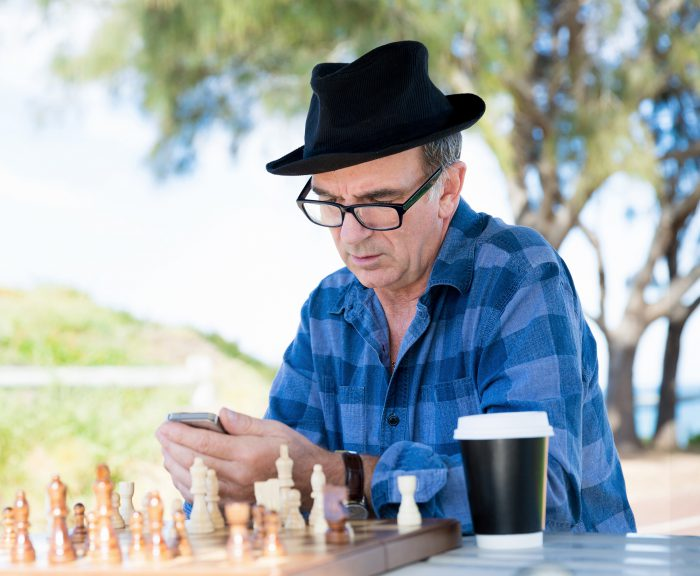 Man with glasses using smartphone and drinking a coffee in outdoor public space
