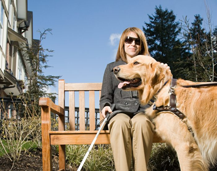 Young woman sat on bench with guide dog and stick