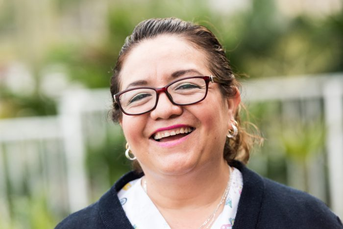 Middle aged women wearing glasses, looking at camera and smiling