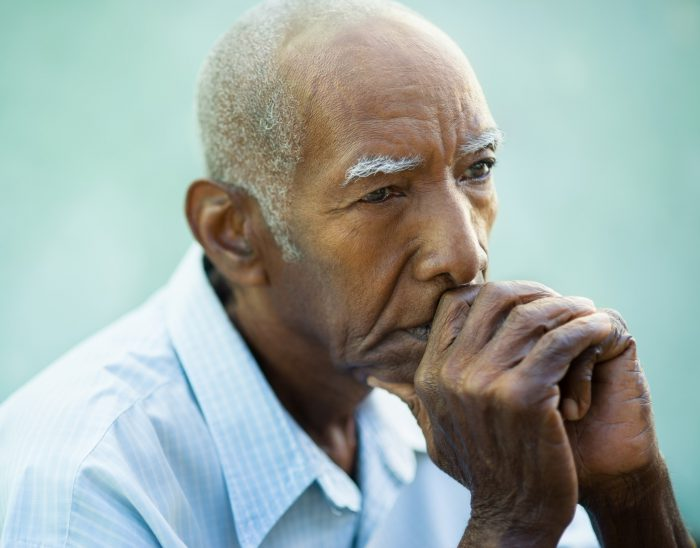 Male pensioner sat with thoughtful expression