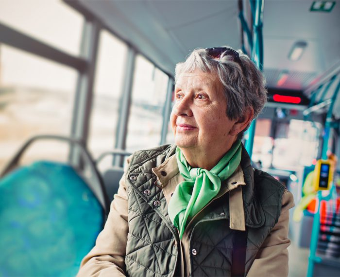 Female pensioner comfortably sitting at front of bus
